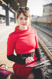 young beautiful red dressed vintage hipster woman at the station using tablet