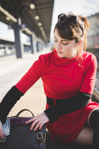 young beautiful red dressed vintage hipster woman at the station