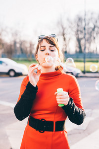 young beautiful red dressed vintage hipster woman in street town playing with bubble soap - childhood, having fun, happiness concept