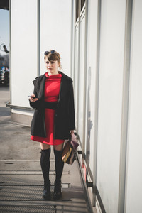young beautiful red dressed vintage hipster woman in street town using smartphone