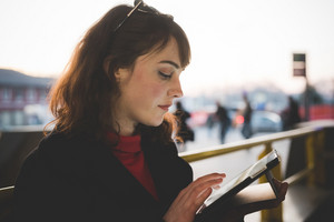 young beautiful red dressed vintage hipster woman in street town using tablet