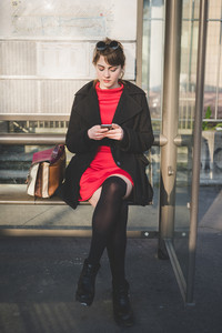 young beautiful red dressed vintage hipster woman in street town waiting bus