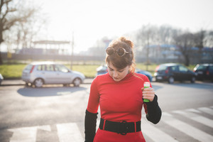 young beautiful red dressed vintage hipster woman in street town