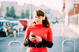 young beautiful red dressed vintage hipster woman outdoor in the city listening music with headphones and smart phone handhold - technology, music concept