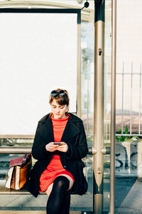 Young beautiful red dressed vintage hipster woman sitting at bus stop using smart phone hand hold tapping touchscreen - technology, commuter, social network concept