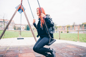 Young beautiful red hair venezuelan woman lifestyle in the city having fun at the playground on a seesaw - happiness, carefree concept