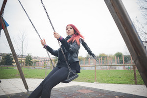 young beautiful red hair venezuelan woman lifestyle in the city of milan having fun at the playground