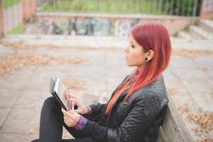 young beautiful red hair venezuelan woman outdoor using tablet hand hold - technology, social network, communication concept