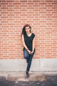 Young beautiful reddish brown hair caucasian girl posing leaning against a wall overlooking right on one leg - carefreeness, freshness, youth concept - dressed blue jeans and black shirt