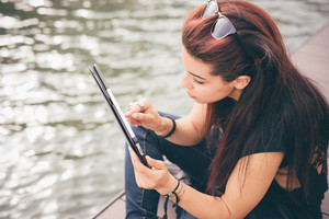 Young beautiful reddish brown hair caucasian girl seated on a sidewalk using a tablet looking the screen - technology, social network, communication concept - dress with black shirt and blue jeans