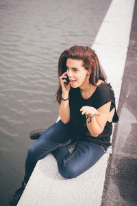Young beautiful reddish brown hair caucasian girl talking smartphone seated on a sidewalk on Navigli, overlooking - technology, social network, communication concept