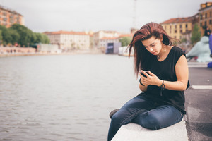 Young beautiful reddish brown hair caucasian girl using a smartphone seated on a sidewalk on Navigli, looking down the screen - technology, social network, communication concept