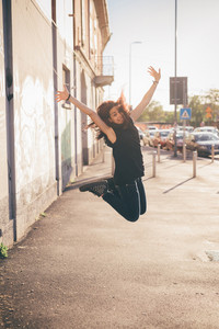 Young beautiful reddish brown hair caucasian woman jumping in the street looking in camera smiling - carefreeness, youth, freshness concept - dressed with blue jeans and black shirt