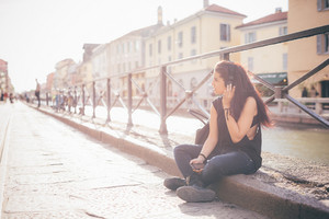 Young beautiful reddish brown hair caucasian woman listening to the music seated on the sidewalk - relax, music, technology concept - dressed with black shirt, overlooking right