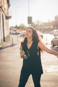 Young beautiful reddish brown hair caucasian woman listening to the music walking through the street - relax, music, technology concept - dressed with black shirt and beer handheld