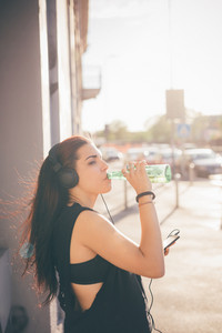 Young beautiful reddish brown hair caucasian woman listening to the music walking through the street - relax, music, technology concept - dressed with black shirt, drinking beer