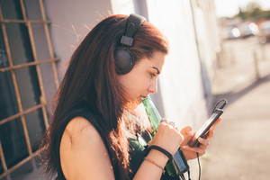 Young beautiful reddish brown hair caucasian woman listening to the music walking through the street - relax, music, technology concept - dressed with black shirt, looking the screen