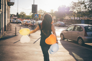 Young beautiful reddish brown hair caucasian woman viewed from back walking through the street playing with baloon in shape of heart - carefreeness, childhood, youth concept
