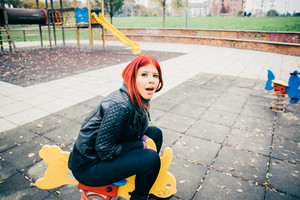 Young beautiful redhead hispanic woman playing in a playground in a park outdoor in the city - carefree, childhood, youthful concept