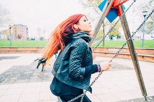 Young beautiful redhead venezuelan woman having fun at the playground riding seesaw, looking over - childhood, happiness, fun concept