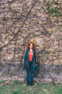 Young beautiful redhead woman outdoor looking camera leaning against wooden wall - pensive, serious, customer concept