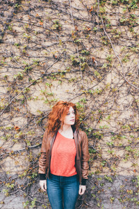 Young beautiful redhead woman outdoor looking over leaning against wooden wall - pensive, serious, customer concept