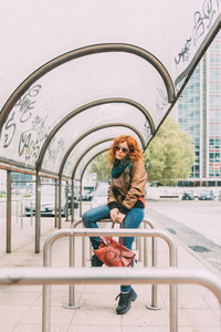 Young beautiful redhead women sitting outdoor in the city overlooking smiling - carefree, happiness, thoughtless concept