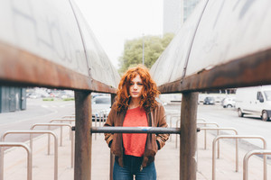 Young beautiful redhead women standing outdoor in the city looking over, serious, hands in pocket - pensive, thoughtful, melancholy concept