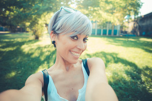 young beautiful short blue hair hipster woman selfie in the city