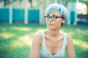 young beautiful short blue hair hipster woman using tablet device in the city