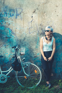 young beautiful short blue hair hipster woman with headphones music and bike in the city