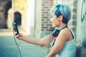 young beautiful short blue hair hipster woman with headphones music selfie in the city