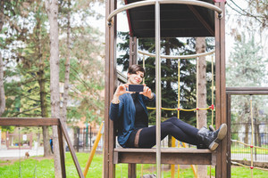 Young beautiful short brown hair woman sitting in a playgroung holding a smart phone taking photos - technology, social network, communication concept