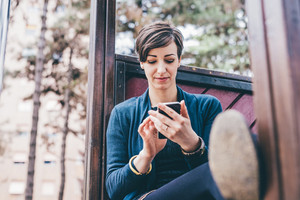Young beautiful short brown hair woman sitting in a playgroung holding a smart phone tapping the screen - technology, social network, communication concept