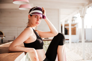 Young beautiful sports woman resting after workout at the beach cafe and looking at camera