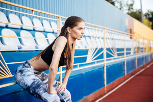 Young beautiful sportswoman leaning on the railing on the stadium