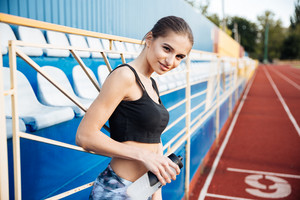 Young beautiful sportswoman with bottle of water leaning on the railing on the stadium