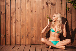 Young beautiful surprised woman in bikini looking away over wooden background