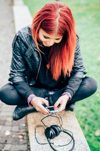 Young beautiful venezuelan redhead woman sitting outdoor holding smart phone, looking down tapping the screen smiling - happiness, having fun, technology concept