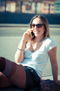 young beautiful woman calling in the city