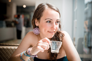 young beautiful woman drinking coffee at the coffee bar