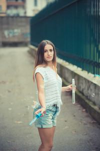 young beautiful woman girl autumn blowing bubbles soup outdoor