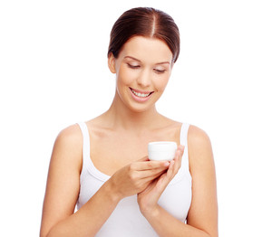 Young beautiful woman holding container with facial or body cream and looking at it