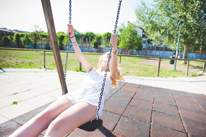 Young beautiful woman in a city park playing swing - enthusiasm, happiness, childhood concept