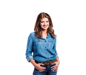Young beautiful woman in blue denim shirt and jeans, hands in pockets. Studio shot on white background, isolated.