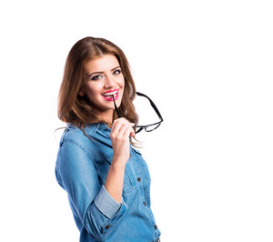 Young beautiful woman in blue denim shirt biting her trendy black eyeglasses, studio shot on white background, isolated