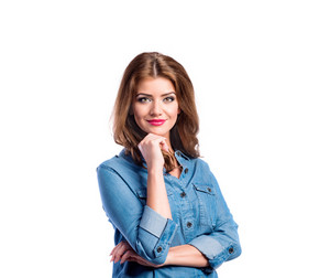 Young beautiful woman in blue denim shirt, holding chin. Studio shot on white background, isolated.