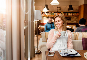 Young beautiful woman in cafe drinking coffee, enjoing her espresso and relaxing