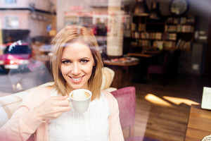 Young beautiful woman in cafe drinking coffee, street reflection in window