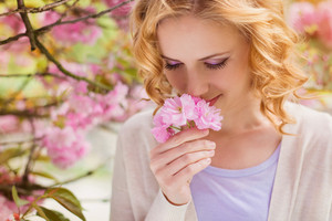 Young beautiful woman in front of a blooming tree